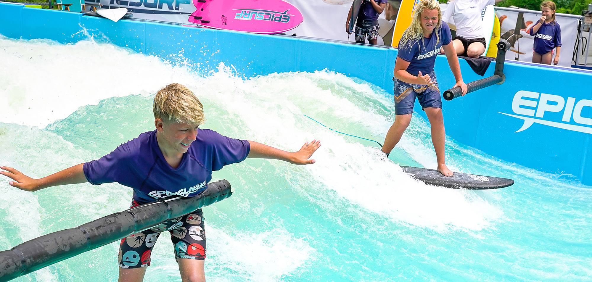 two boys learning to surf on epicsurf training bars stationary wave